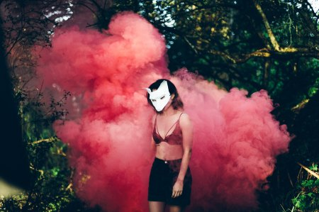 Girl with wold mask in front of pink smoke